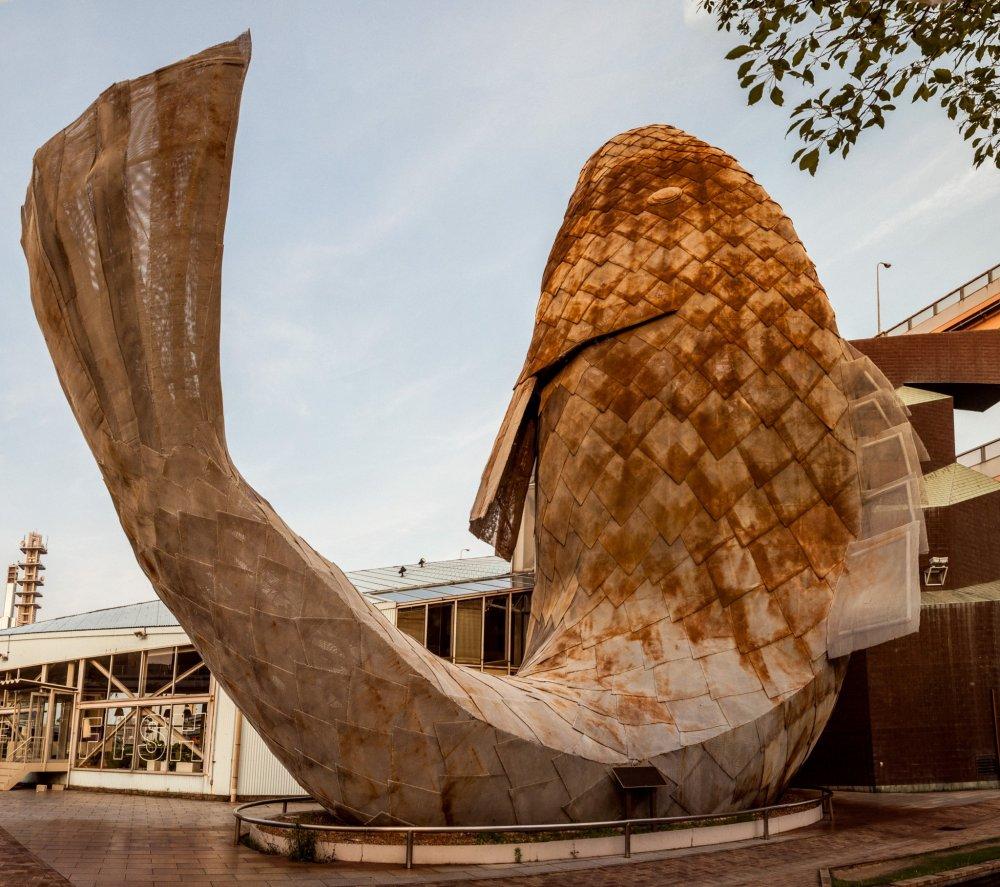 Ikan jala raksasa berdiri di depan Cafe Fish! Ikan koi yang dibuat oleh Frank O. Gehry ini digambarkan tengah menari.