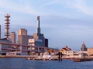 Kota dan pelabuhan memancarkan cahaya saat matahari terbenam, menjadikan area ini sebagai lokasi yang bagus untuk mengamati bangunan tinggi di Kobe
