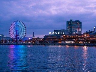 Distrik hiburan dan perbelanjaan Harbourland yang berada di sekitar, memancarkan cahaya yang mengundang pada malam hari