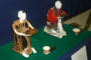 A stripped tea serving mechanical doll, and one fully clothed.