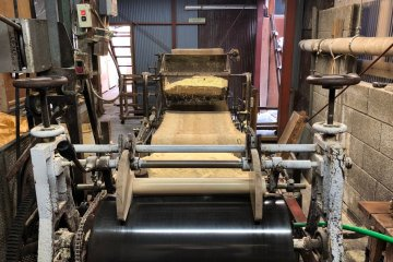 Dye press machine topped with heaps of sawdust