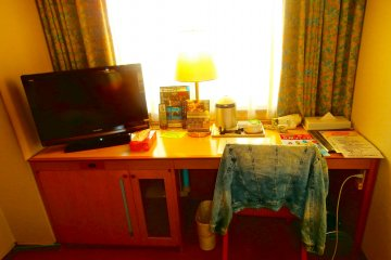 A nice long desk with a liquid crystal television, and under the desk is a foot massage machine
