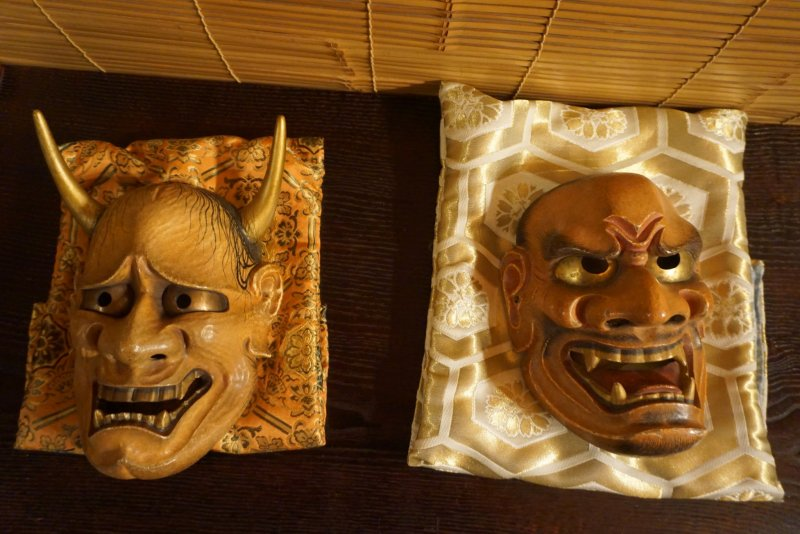 Wooden masks depicting a female demon (left) and an ogre (right)