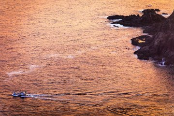 A fishing boat heads out to sea past the rocky cliffs of Kamigoto