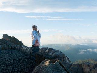 眼下に迫る急峻な岩場で合掌し、一心不乱に経文を唱えるご婦人