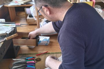 A grumpy craftsman polishing his blades