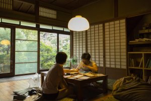 Two guests sit in the common space that overlooks a beautiful garden