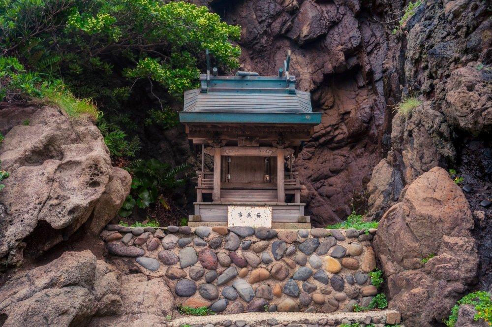 Một ngôi đền khuất sau những tảng đá gần bãi biển Kuniga