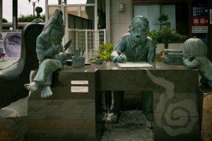 รูปปั้นหินกับทองแดงขนาดเท่าตัวจริง ของอาจารย์มิซุกิขณะทำงาน โดยมีตัวละครในเรื่องนั่งอยู่ข้างๆ