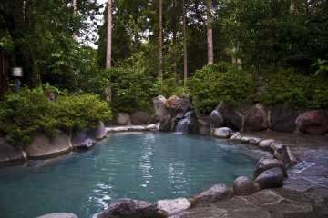 The Men's Rotenburo (open-air hot spring) is surrounded by trees.