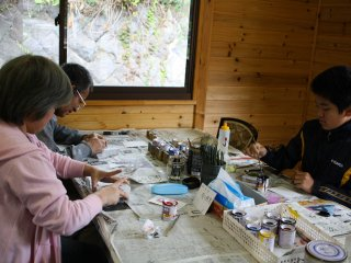 A small family concentrating on their Kusatsu limestone masterpieces