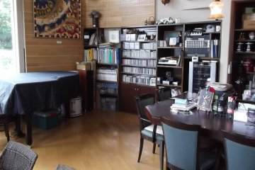 <p>Lots of CDs and sheet music sit behind the piano</p>