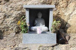道路向かいの岩の上には小さな石仏が祀られてあった