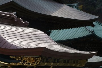 Roof of Hojo. It used to be the head priest's living quarters, but is now a room for Za-zen training. Take of your shoes, and go into the building. A wooden walkway encircles the main room. A Zen garden sits in back of the room. There are several benches