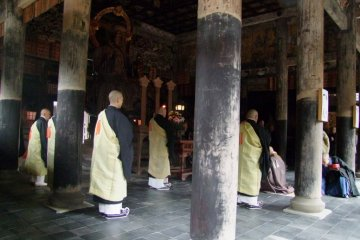 Priests wearing light yellow robes had been standing patiently, waiting for the chief priest. Flames of candles on the altar were flickering. Then, the chief priest came into the hall. A solemn low tone of voices began to chant.