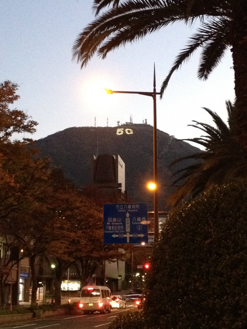 """走出八幡站后远望到的皿仓山,为了纪念北九州市制50周年,皿仓山山体上点缀着巨大的""""50""""字样"""