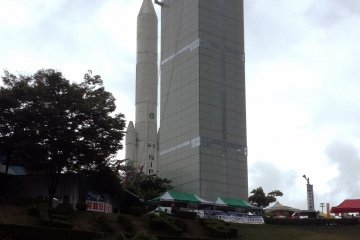 <p>The Space Tower stretches towards the sky&nbsp;right alongside a model rocket used to launch satellites to the heavens.&nbsp;</p>