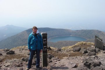 The author on one peak of the Kirishima range with a crater lake in the background