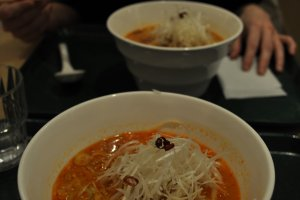 White ramen includes sesame, thick green onions, and bean sprouts in a spicy broth