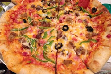 <p>The Surfside Special Pizza is made in Okuma&#39;s outdoor pizza oven and comes with&nbsp;pepperoni, ham, bacon, sausage, peppers, onions, mushrooms and black olives smothered with cheese</p>