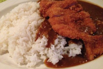 <p>The Surfside&#39;s Special Blend Curry sauce on a large chicken cutlet with steamed rice</p>
