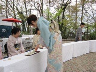 Одетая в прекрасное элегантное кимоно, одна из участниц церемонии грациозно подает чай
