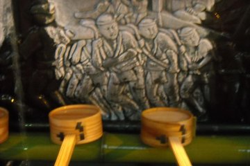 Yamakasa racers carved into water basin.
