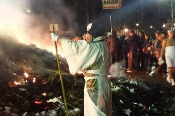 <p>A priest oversees the bonfire. Unlike participants, he is fully clothed.&nbsp;</p>