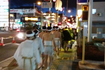 <p>A traditional festival in progress is juxtaposed against a busy city street.&nbsp;</p>