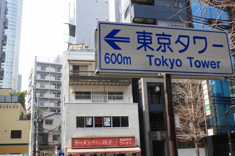 """จากสถานีHibiya H07 (จากพระราชวังอิมพีเรียล)ไปตามHibiya line สายสีเทาอ่อนเพียงสองสถานีลงที่สถานี Kamiyacho H05 Exit 1ก็สามารถมองเห็นป้ายบอกทางได้อย่างชัดเจน """"600m Tokyo tower"""""""