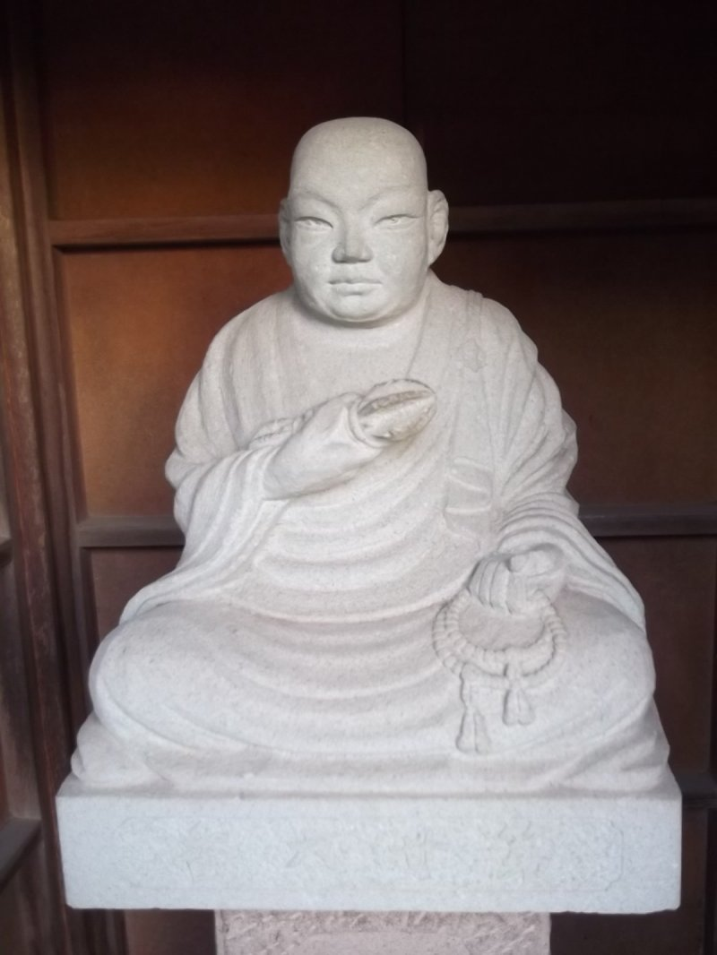 <p>Sitting serenely in his shelter near the entrance to one of the temples</p>