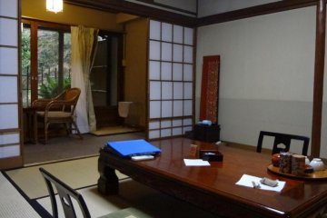 The simple tatami room was not large, but big enough for the two of us. The shoji sliding door opened onto a stone-lined bath, which was overflowing with hot water