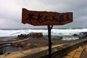 A sign reads Furofushi Onsen. That ramshackle shelter in the background that looks like it will be washed away by the next big wave is your destination.