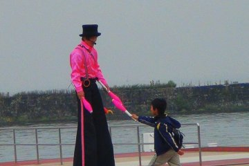 <p>The &quot;trickman&quot;. He entertains the visitors and passengers with his tricks while the boat is being prepared for boarding.</p>