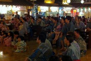 ภาพครอบครัว คู่รักชาวญี่ปุ่นที่แต่งตัวด้วยชุดยูกาตะนั่งชมการแสดงในบรรยากาศย้อนยุค
