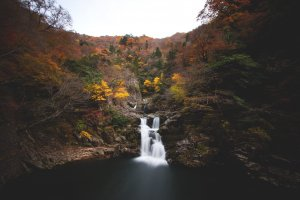 Waterfall flowing in the middle of rocky mountains in Sandankyo gorge, Japan